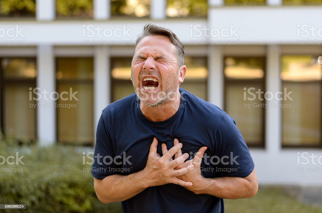 Middle-aged man suffering a heart attack royalty-free stock photo