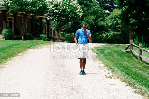 istock Middle-aged man walking down a road 803131382