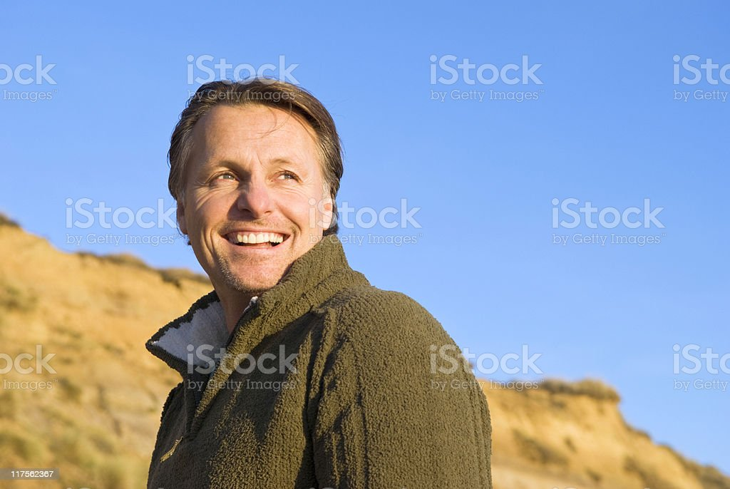 Middle-aged man wearing a thick coat smiling under blue sky royalty-free stock photo