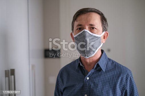 Middle-aged man wears face mask in the Coronavirus  Covid19 pandemic