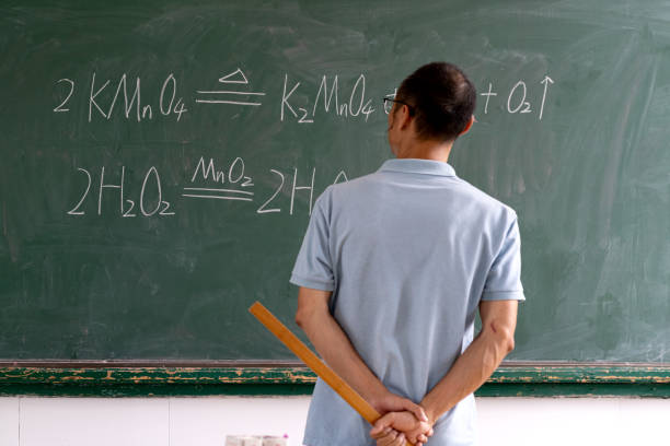 middle-aged man with hands behind his back in front of blackboard - engenharia química imagens e fotografias de stock