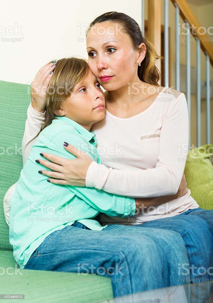 middle-aged mother comforting teenage boy stock photo