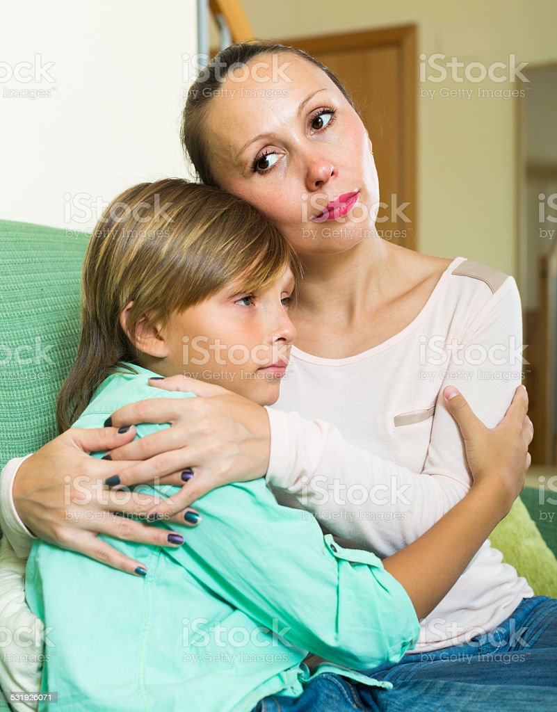 middle-aged mother consoling sad  son stock photo