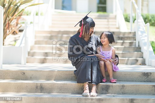 Attractive Filipino woman in graduation robe and cap sits on steps with her young daughter after graduation. They are looking at each other affectionately.