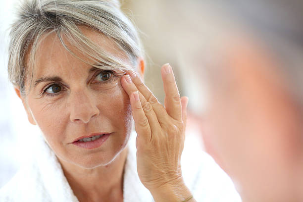 middle-aged woman applying cream on face - concealer stockfoto's en -beelden