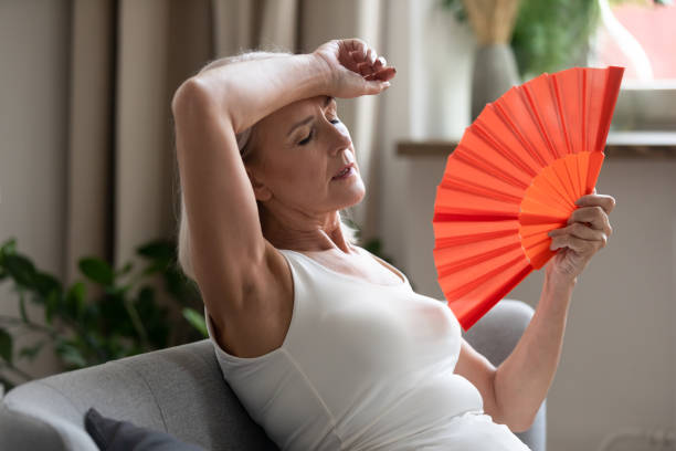 Middle-aged woman cooling herself with hand fan indoors Middle-aged woman leaned on sofa resting in living room cools herself with orange colour hand fan touch forehead feels unwell suffers from unbearable hot summer weather at home without airconditioner hormone stock pictures, royalty-free photos & images