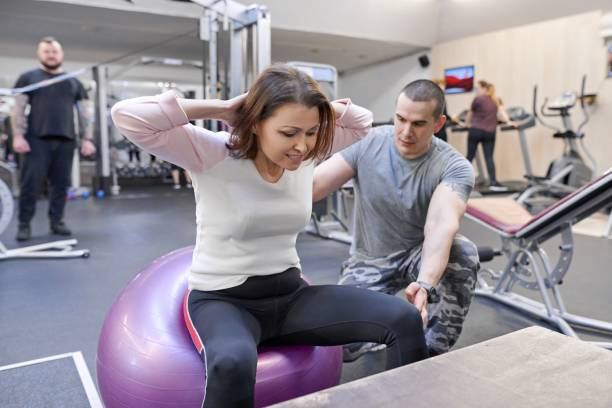 middle-aged woman doing sports exercise in fitness center. personal gym trainer assisting mature woman. health fitness sport age concept - sports medicine stock pictures, royalty-free photos & images