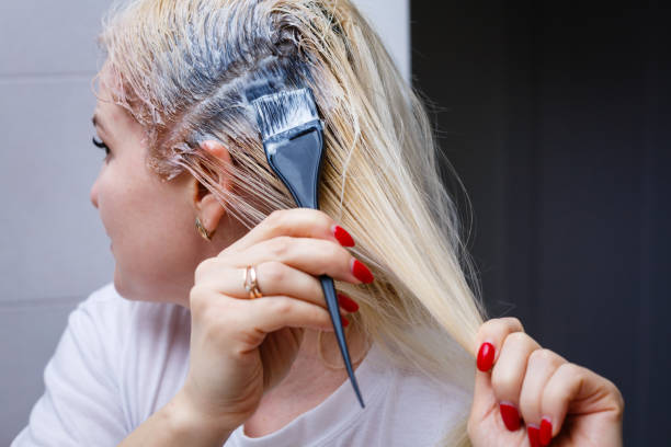 A middle-aged woman dyes her hair at home, indoors stock photo