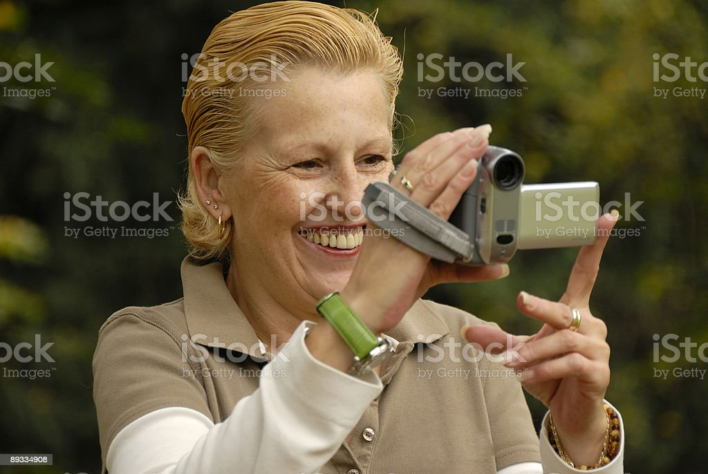 middle-aged woman filming with a handycam stock photo