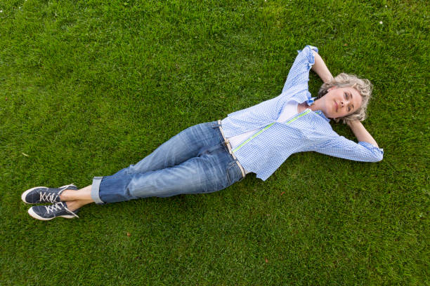 middle-aged woman in casual weekend clothing relaxing on a grass lawn in a yard or park. she is smiling with a happy, contented expression and looks like she is daydreaming. - reclining stock photos and pictures
