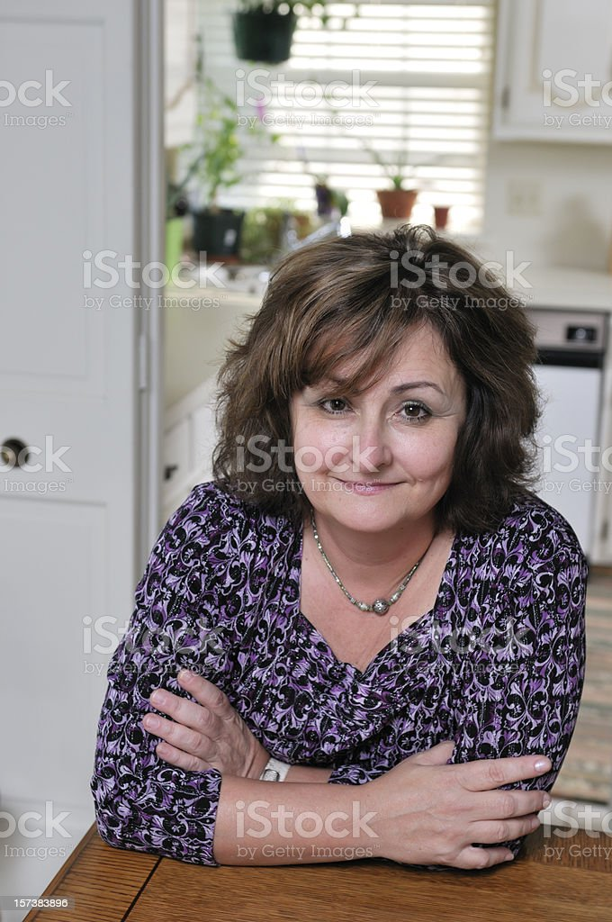 Middle-aged woman in kitchen royalty-free stock photo