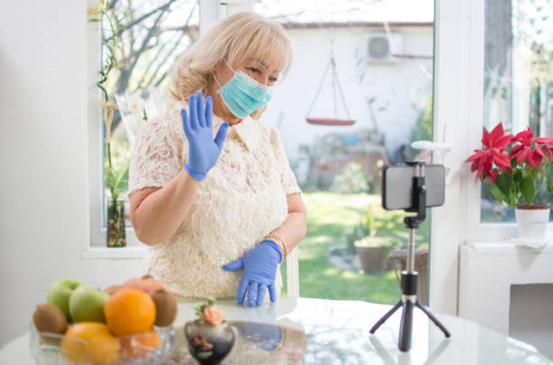 Middle-aged woman in quarantine for coronavirus. Mid age woman wearing protective mask and gloves waving hand to her family during video call on smart phone at home stock photo