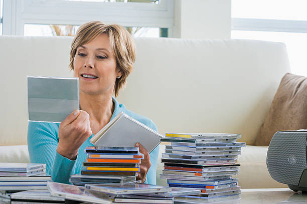 middle-aged woman looking at music cds - disposition photos et images de collection