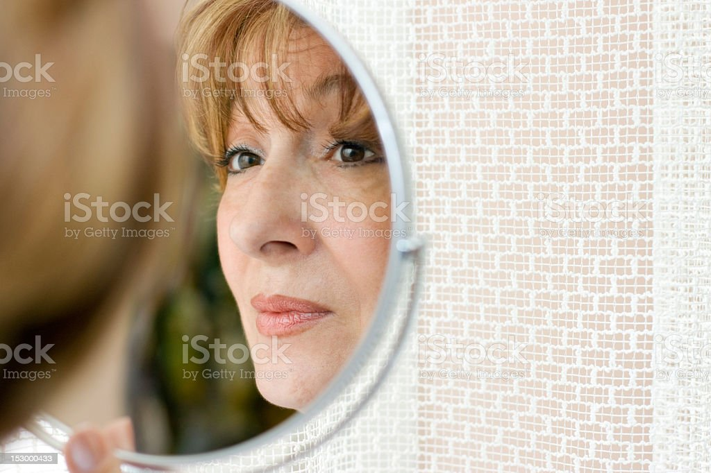 Middle-aged woman looking into the mirror royalty-free stock photo