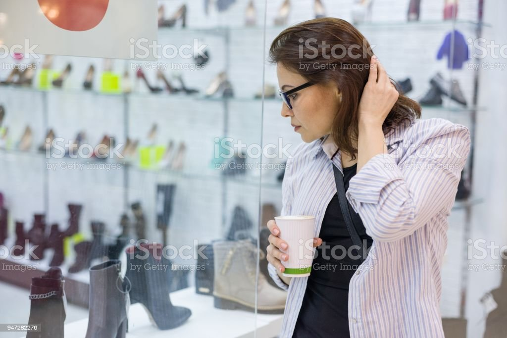 Middle-aged woman looks at the shoe showcase in the shopping mall stock photo