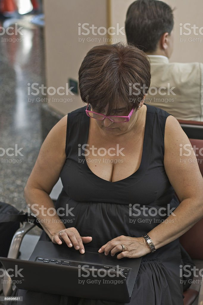 Middle-aged woman manager checking email in the airport royalty-free stock photo
