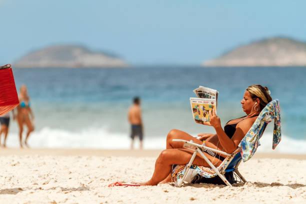 middelbare leeftijd vrouw leest het nieuws in de krant terwijl u geniet van de zonnige dag in copacabana beach - newspaper beach stockfoto's en -beelden
