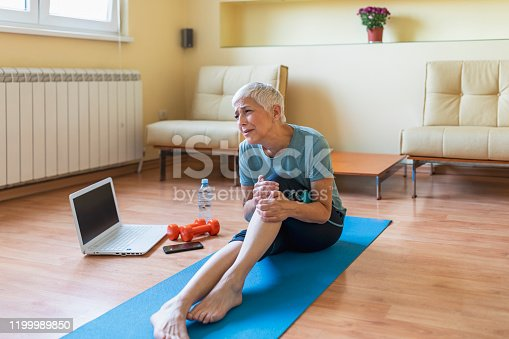 Unhappy Mature woman sitting on the mat .