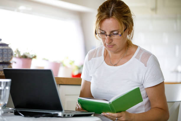 Middle-aged woman using laptop at home stock photo