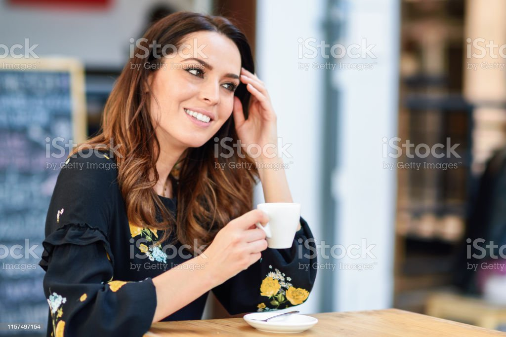 Middle-aged woman drinking coffee in an urban cafe bar. Young female...