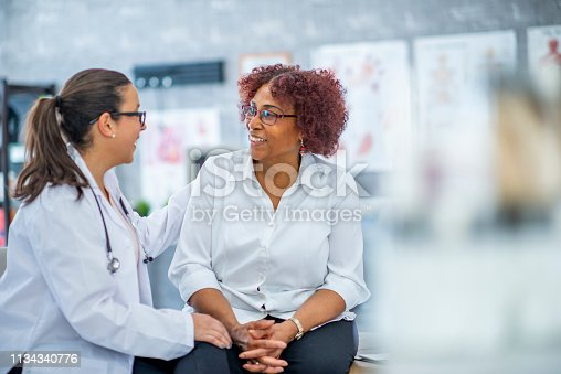 An African American woman smiles lightly as she discusses with the doctor sitting beside her. They are in a medical office.