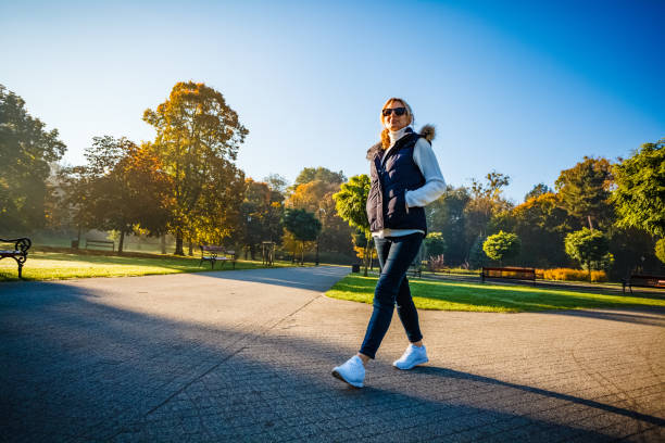 Middle-aged woman walking in city park stock photo