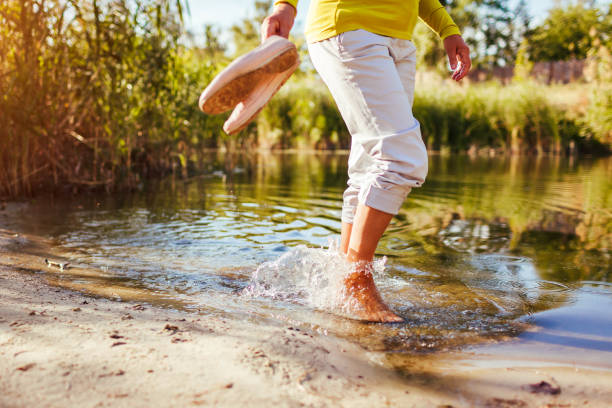 Middle-aged woman walking on river bank on autumn day. Senior lady having fun in the forest enjoying nature. Closeup