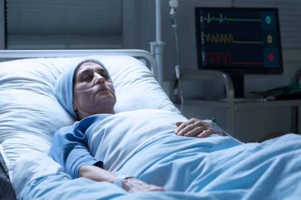 Middle-aged woman with cancer dying Middle-aged woman with cancer dying alone in palliative ward of hospital and heart rate monitor in the background axis deer stock pictures, royalty-free photos & images