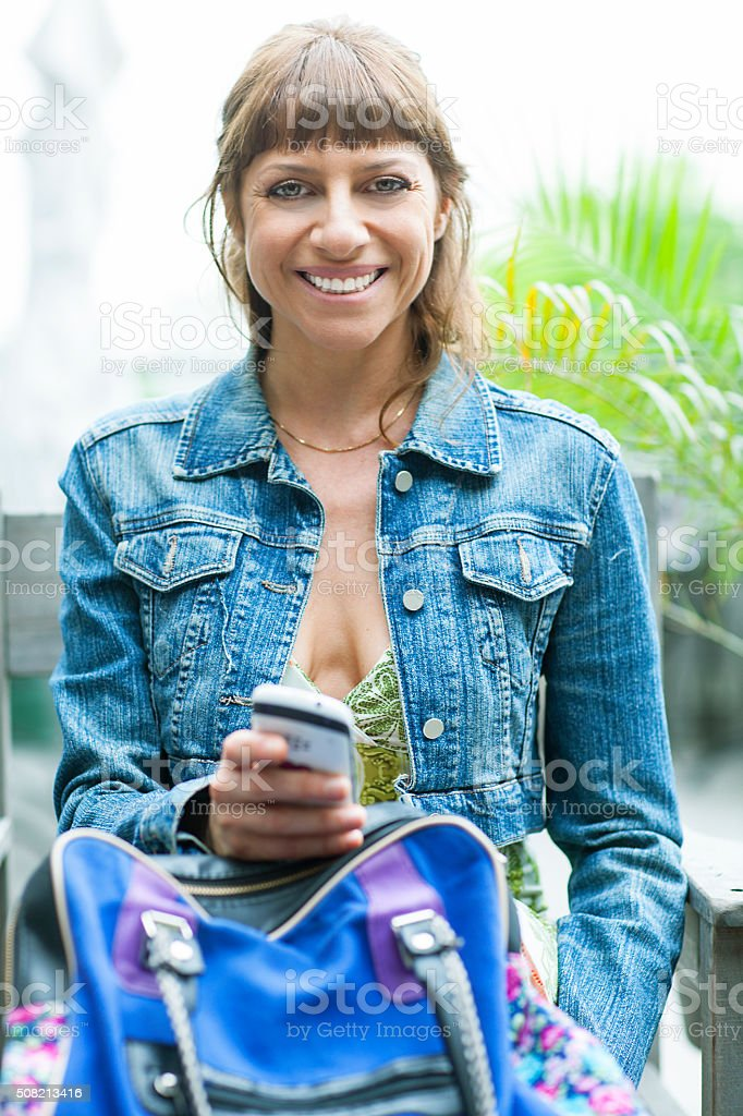 middle-aged woman with cellphone on nature background stock photo