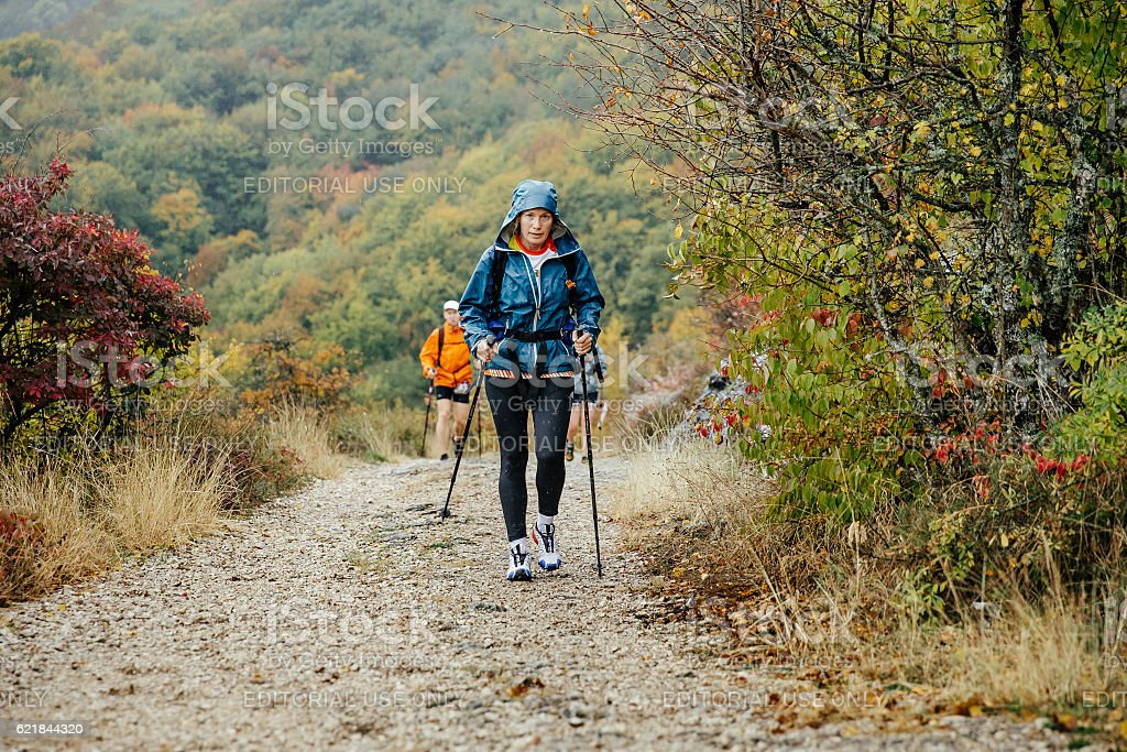 middle-aged woman with walking poles traveling in rainy weather stock photo