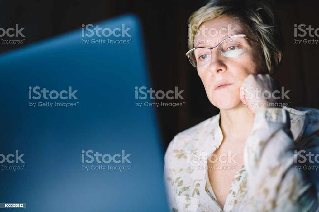 Middle-aged woman working on laptop stock photo