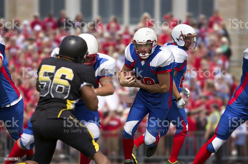 Mid-game photo of a football player carrying the ball royalty-free stock photo