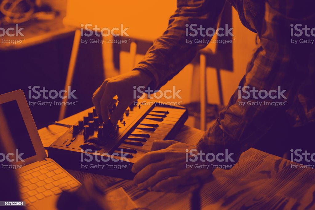 Midi keyboard and laptop - the process of recording sound and music. Duotone effect - orange and purple colors stock photo