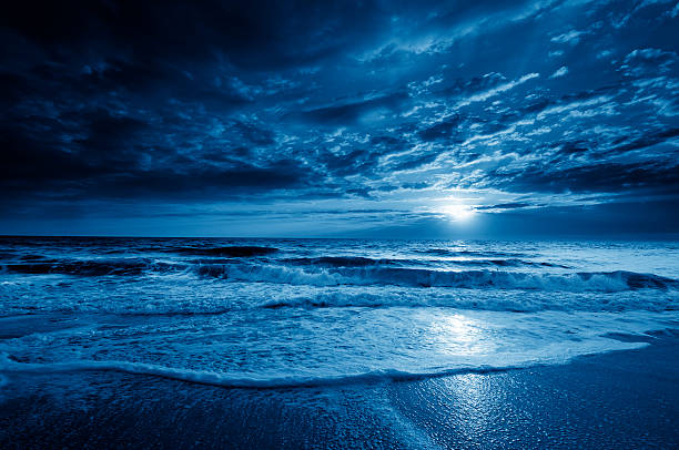 midnight blue coastal moonrise with dramatic sky and rolling waves - romantic moon stock photos and pictures