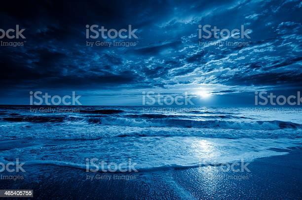 Photo of Midnight Blue Coastal Moonrise With Dramatic Sky and Rolling Waves
