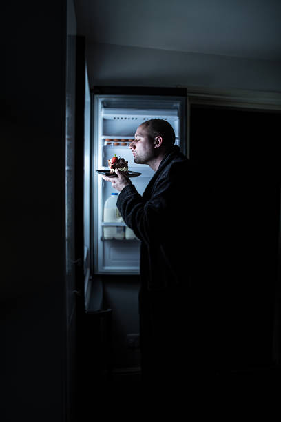 Midnight Cake Snacking a bald man in his dressing gown sniffing and savouring a slab of cake left in the fridge. midnight stock pictures, royalty-free photos & images
