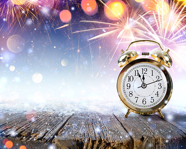 Midnight Celebration - turn of the year Clock On Snowy Table With Fireworks.. midnight stock pictures, royalty-free photos & images