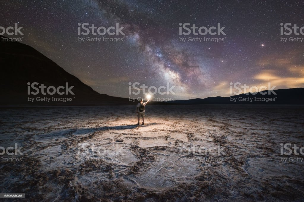 Midnight Explorer illuminating Badwater Basin at night stock photo