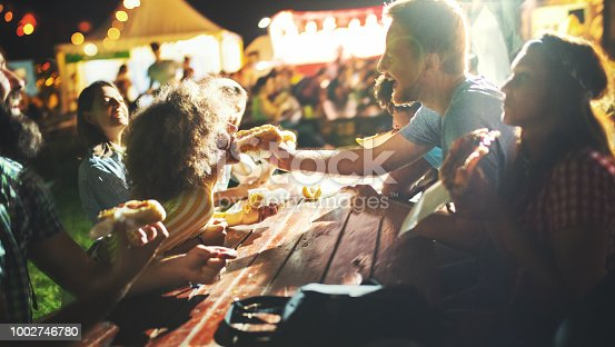 Closeup of group of young adults having a snack on a night out. They are sitting outdoors at a festival, having fun while eating hot dogs and pizzas.
