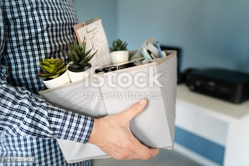 1181817161 istock photo Midsection close up of unknown caucasian man holding a box with personal items stuff leaving the office after being fired from work due recession economic crisis downturn losing job company shutdown 1217889456