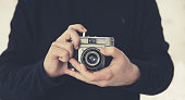 A midsection of a male photographer focussing the lens whilst holding a retro or old fashioned 35mm camera