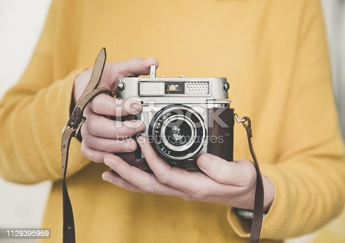 A midsection of a girl holiding a vintage, 35mm camera in yellow with copy space