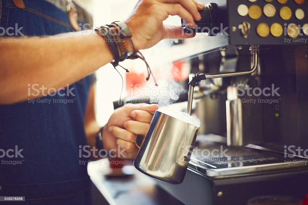 Midsection of barista steaming milk in cafe stock photo