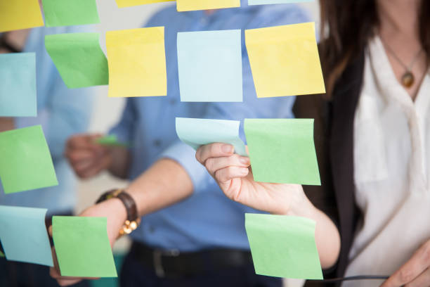 midsection of business people sticking adhesive notes on glass - adhesive note stock photos and pictures