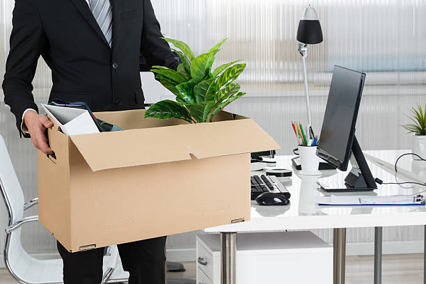Midsection Of Businessman Carrying Cardboard Box Midsection of businessman carrying cardboard box by desk in office downsizing unemployment stock pictures, royalty-free photos & images
