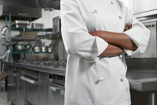 Midsection Of Chef With Arms Crossed Closeup midsection of a female chef with arms crossed in kitchen chef's whites stock pictures, royalty-free photos & images