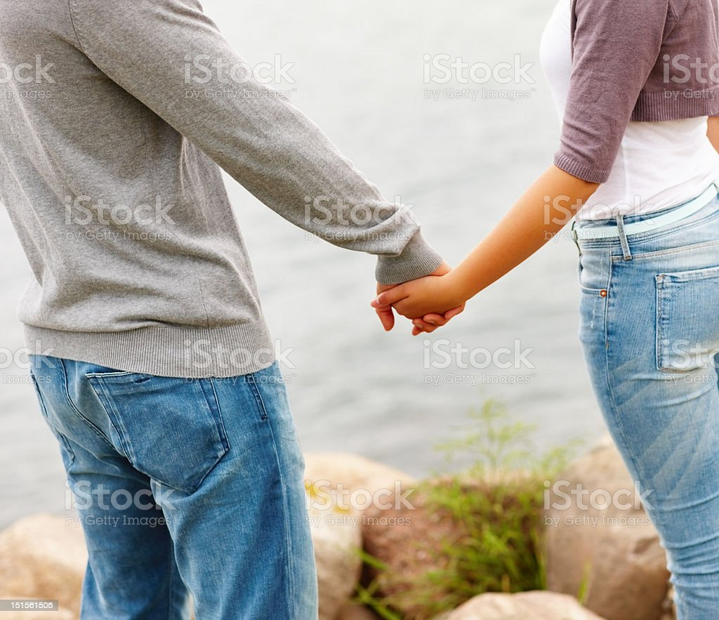 Midsection of couple holding hands outdoors royalty-free stock photo