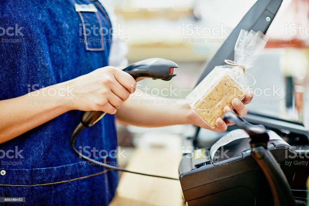 Buik van deli eigenaar scanning barcode op verpakking foto