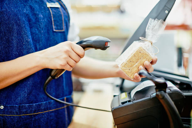 Midsection of deli owner scanning barcode on food package stock photo