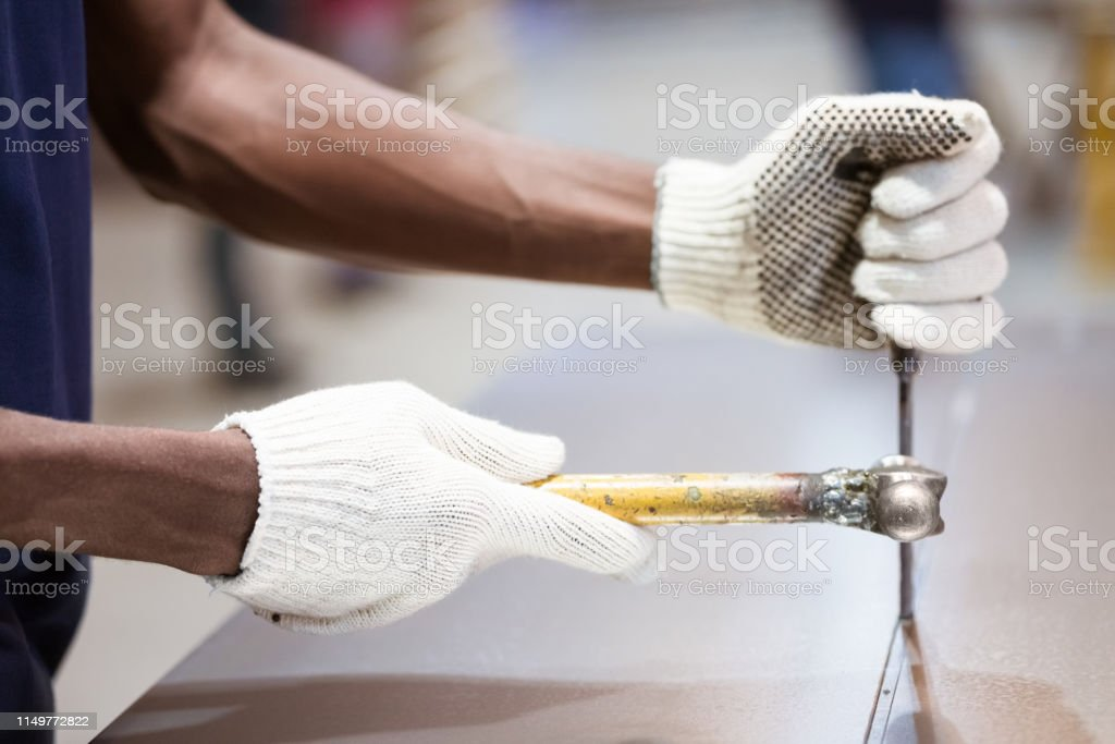 Midsection of engineer hammering machine part Midsection of male apprentice hammering on metal sheet. Engineer is wearing gloves while using work tool. He is working in factory. 25-29 Years Stock Photo